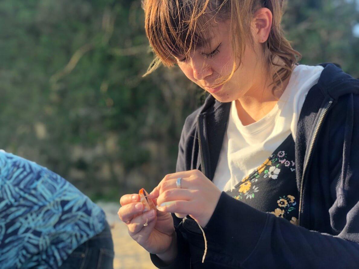 「自分で収穫したシークヮーサーを友人にプレゼントしてシークヮーサーの魅力をもっと知ってもらい、来年は友人と一緒に収穫のお手伝いに来たい」と話す赤崎円香さん(写真は、ツアー1日目に交流を図るため、沖縄の海まで散歩し、貝殻でアクセサリー作りを行った時の一枚)