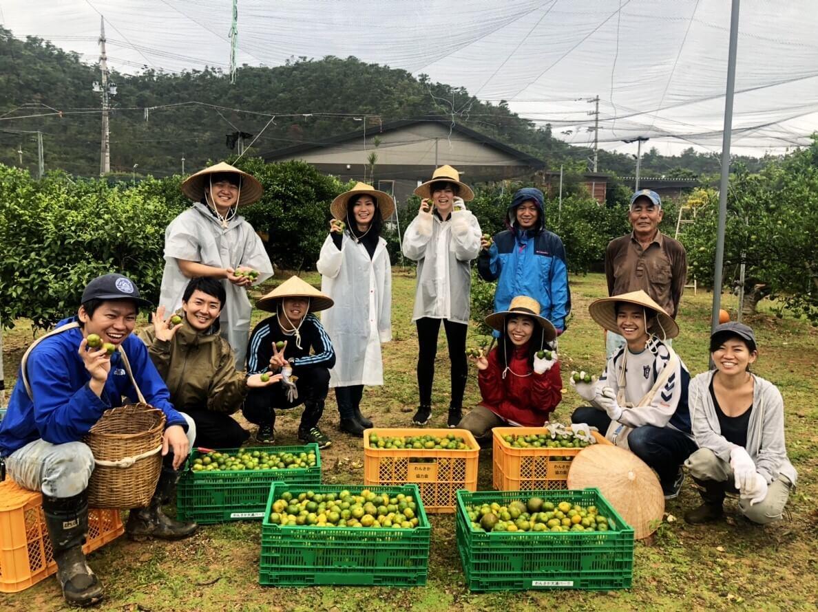 収穫体験先である上里さんと畑で、無事に全てのシークヮーサーを収穫しきり、全員が安心したところで撮影した一枚