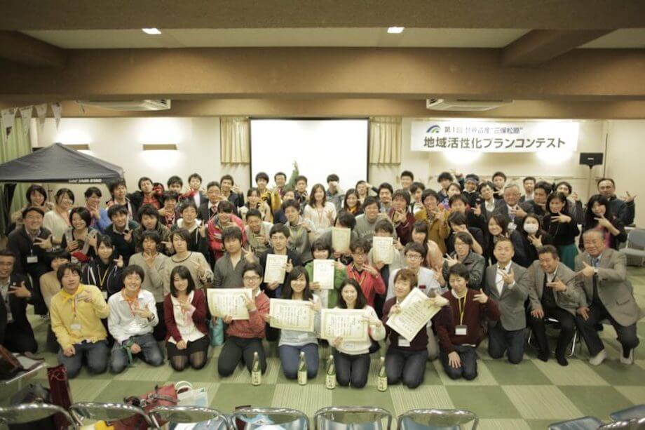"""住吉氏が思い出の品として持ってきてくれたのは、こちらの一枚の写真。住吉氏が全国の大学生を静岡に集めて「地域活性化プランコンテスト」を行ったときの最後の集合写真。ここには、参加者である県外の大学生はもちろん、県内の大学生、コンテストを見にきてくれた地域の皆さん、イベントに協賛をしてくれた地元企業の方々、メンターとしてコンテストに関わってくれた都内大手企業の社員の方々、審査員が写っているそう。「コンテストをきっかけに """"3つのしみん"""" が写っているこの写真が好きなんです」(住吉氏)"""