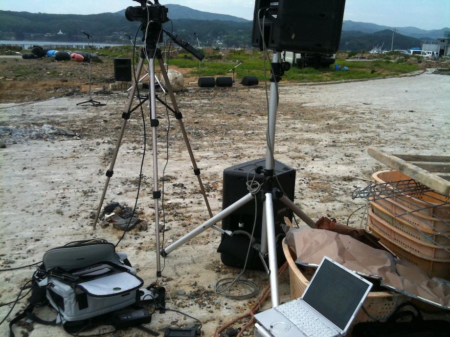 震災後の南三陸にて。月命日に行われる追悼集会の模様を各避難所の住民に向けてライブ配信を行った。