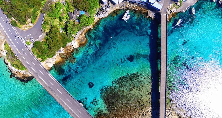 柏島を上空から撮影した写真。海の透明度の高さから、港や周辺の海域の「船が宙に浮いて見える」と、SNSで多くの話題を集めている観光スポット。実際に訪れると、橋の上からでも「肉眼で」水面の底や、泳いでいる魚を見つけることができるから驚きます・・・!